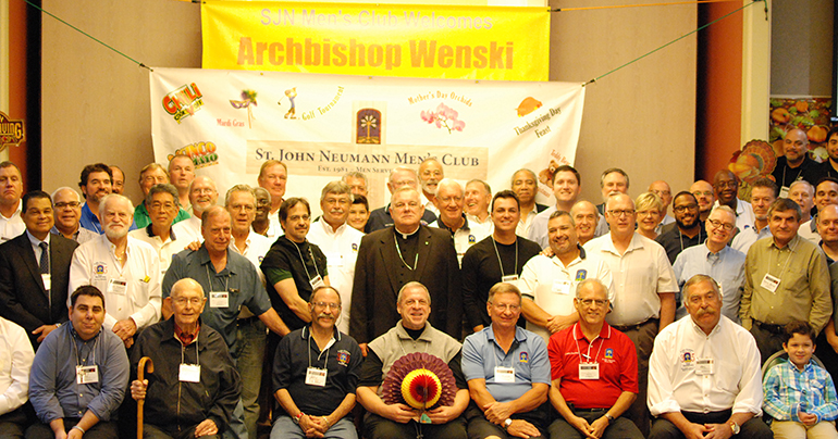 Archbishop Thomas Wenski poses for a picture with members of St. John Neumann's Men's Club during a visit Nov. 6. Seated underneath the archbishop is St. John Neumann's pastor, Father Pablo Navarro.