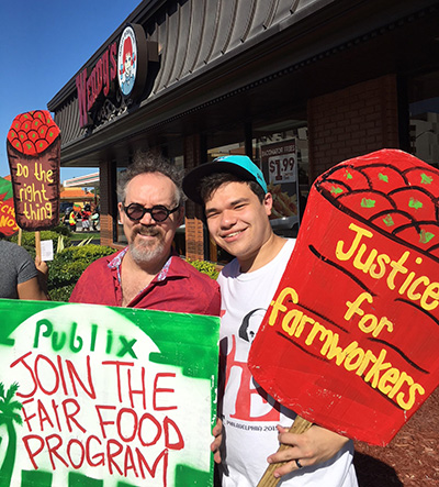 St. Thomas University philosophy professor Darrell Arnold, left, poses with theology student Alberto Rodriguez during the Nov. 11 Miami March for Fair Food.