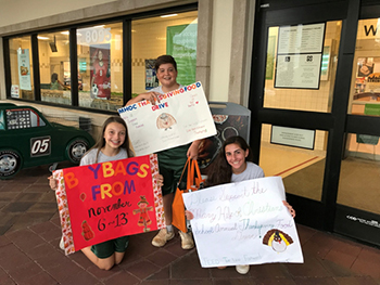 Mary Help of Christians eighth-graders advertise their Thanksgiving food drive at the neighborhood Publix.
