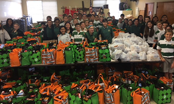 Eighth-grade students at Mary Help of Christians School pose with the 410 bags of food they collected for Our Lady Queen of Heaven's food pantry.