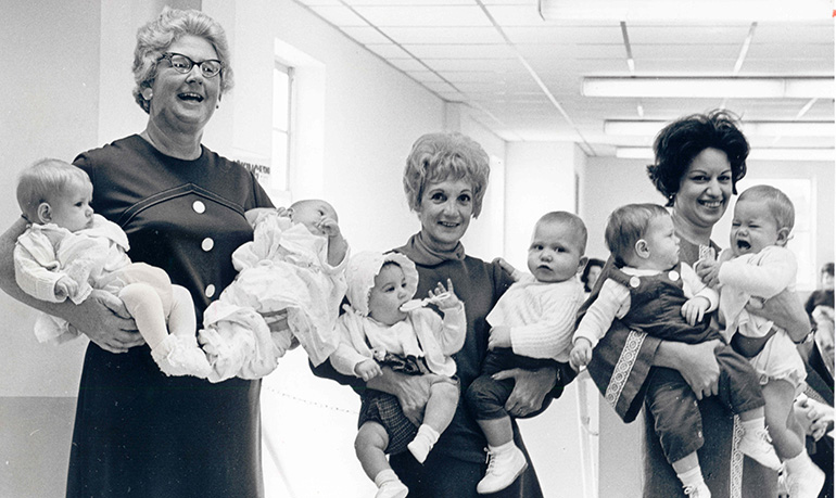 In this Florida Catholic file photo, members of the Catholic Welfare Bureau's adoption staff pose in 1958 with babies they placed for adoption. The Miami archdiocese recently relaunched its adoption program. The agency then known as the Catholic Welfare Bureau is now called Catholic Charities.