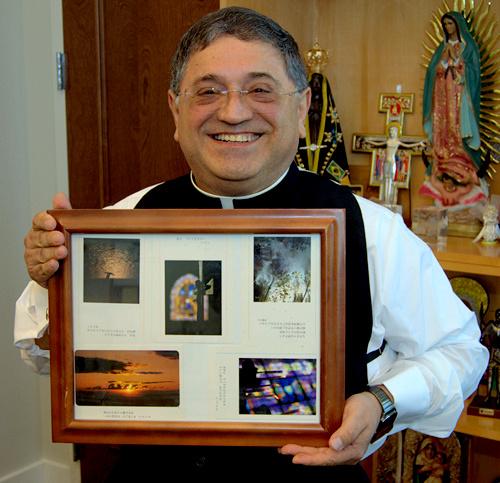 El Obispo Enrique Delgado muestra recuerdos de su viaja a Tokio, que incluye la foto de una cruz que lo inspiró a convertirse en sacerdote.