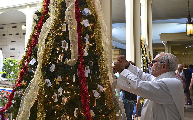 Deacon Jose Naranjo blesses a Christmas tree during a lighting ceremony at Our Lady of Mercy Cemetery in Doral.