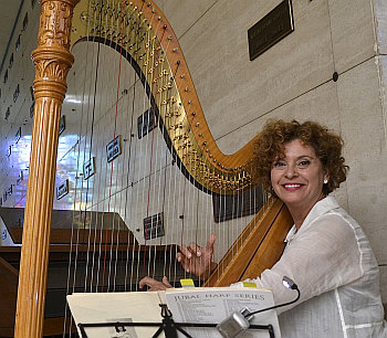 Harpist Trudy Faust provides music at the annual Christmas tree lighting ceremony at Our Lady of Mercy Cemetery in Doral.