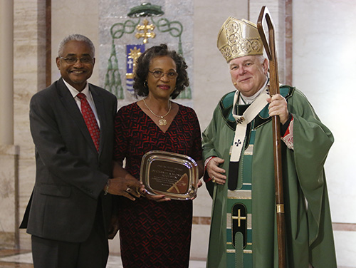 Ducarmel and Monique Augustin of St. Helen Church in Fort Lauderdale receive the 2017 One in Faith award from Archbishop Thomas Wenski. Archbishop Thomas Wenski celebrated the annual ThanksForGiving Mass Nov. 19, thanking all the donors to ABCD, honoring three families with the One in Faith, One in Hope and One in Charity award and inducting new members into the Archbishop Coleman Carroll Legacy Society.