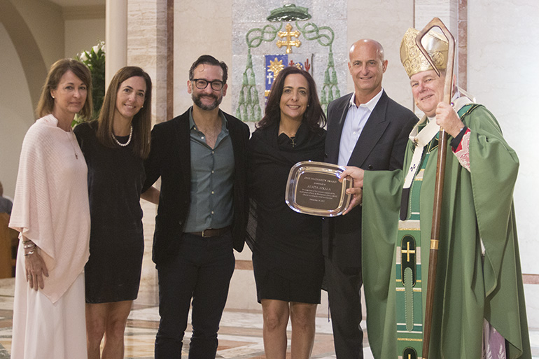 The children of Alicia Aixala of Epiphany Parish in Miami receive their mother's posthumous One in Charity award from Archbishop Thomas Wenski. From left: Ali, Diana, Alex, Mari and Michael Aixala.
