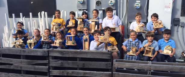 The fourth grade students of Sts. Peter and Paul School show off their solar-powered houses.