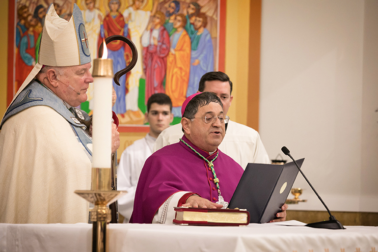 Bishop-elect Enrique Delgado takes an oath of fidelity and signs documents at St. Katharine Drexel Parish in Weston during solemn vespers on the eve of his ordination as the newest auxiliary bishop of the Archdiocese of Miami. At left is Archbishop Thomas Wenski, and at right is his master of ceremonies, Father Richard Vigoa.