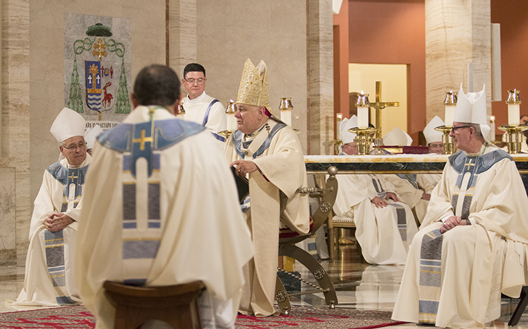 Bishop-elect Enrique Delgado, his back to the camera, listens as Archbishop Thomas Wenski delivers his homily at the ordination Mass. Seated at either side of the archbishop are his co-consecrators, Bishop Felipe Estevez, left, of St. Augustine, and Bishop John Noonan of Orlando, both former archdiocesan priests.