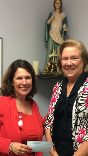 Good News ! Book Fair founder Lizette Lantigua, left, hands a $ 300 donation to Joan Crown, archdiocesan director of Respect Life.