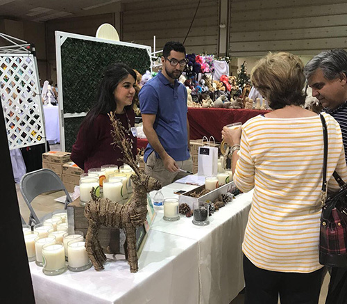 Vanessa Ruiz and Roger Ramirez sell Soy Luz candles at a recent event.