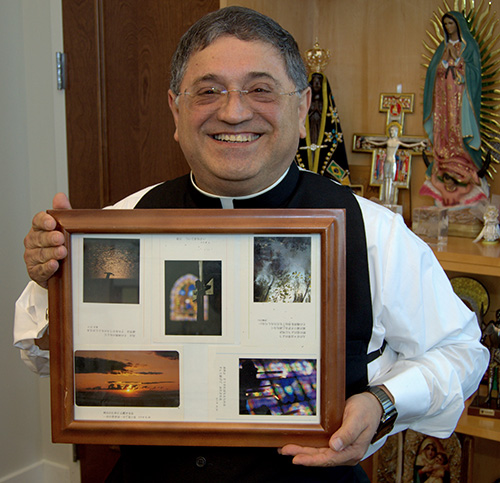 Bishop Enrique Delgado shows a plaque from Sophia University, Tokyo, that includes the photo of a cross that inspired him to become a priest.