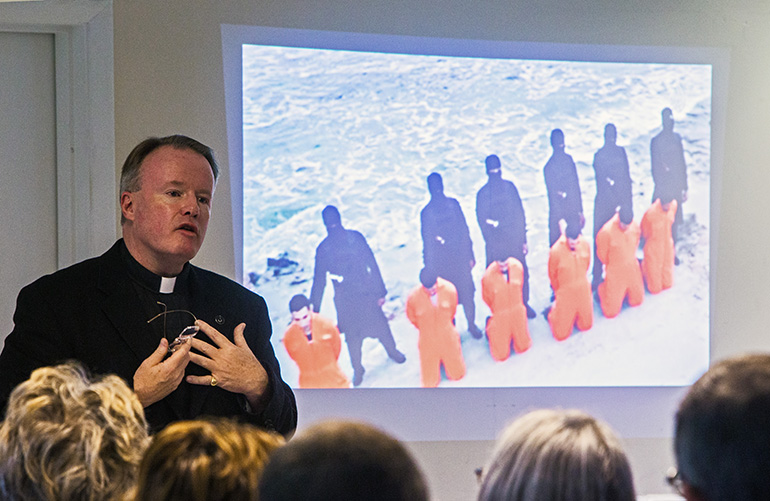 Father Benedict Kiely addresses the audience as a slide presentation displays Coptic Christians about to be martyred by beheading by Islamic terrorists in Lybia. The priest spoke Dec. 11, 2017 at St. Agnes Church, Key Biscayne, about the persecution of Christians in the Middle East.