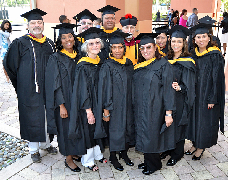 The first 10 graduates of the master's program in bioethics pose before receiving their diplomas Dec. 16 at St. Thomas University. In the back, in the red-topped hat, is Father Alfred Cioffi, director of the program.