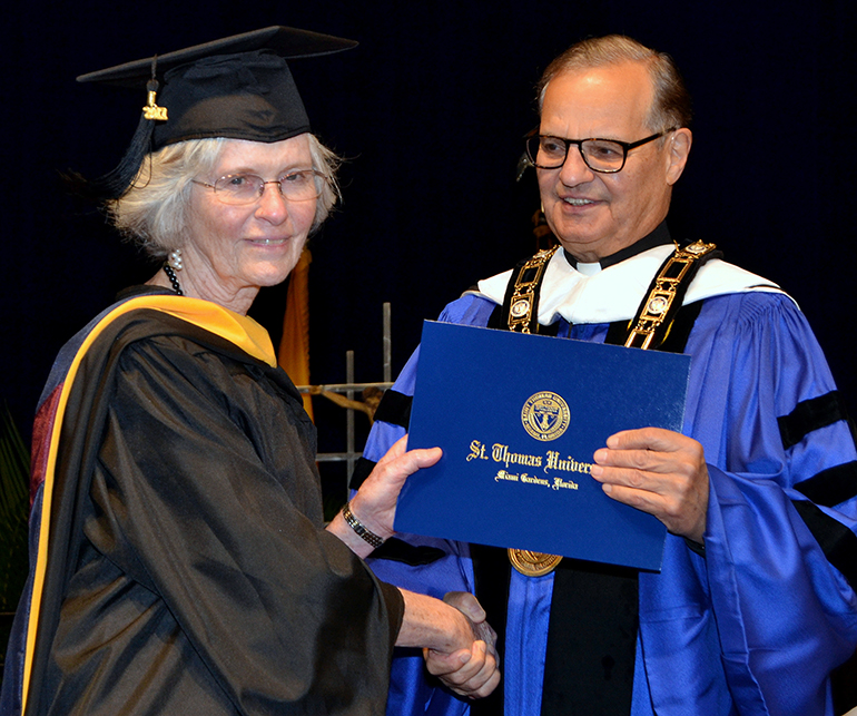 Dr. Mary Jo O'Sullivan receives her diploma in bioethics Dec. 16 from Msgr. Franklyn Casale, president of St. Thomas University.
