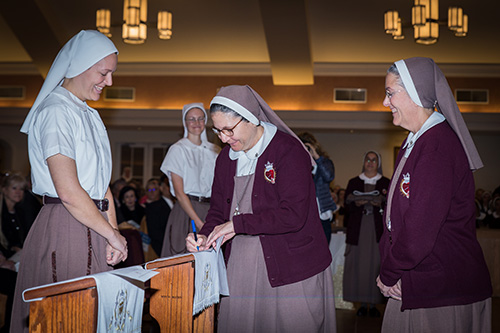 Sister Mary Rachel Hart smiles as Sister Ana Margarita Lanzas, the community's vicar, signs the Formula of Profession, and Mother Adela Galindo, superior and foundress, looks on.