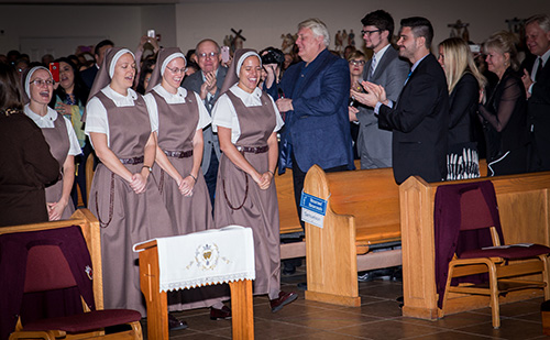 The assembly welcomes back the new sisters, now wearing their religious habit. From left: Sister Clare Marie Bailey, Sister Mary Rachel Hart, Sister Brittany Rose Samuelson, and Sister Alexia Maria Zaldivar-Boillat.
