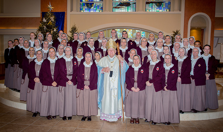 The entire community of Servants of the Pierced Hearts, including the newly professed sisters, pose with Archbishop Thomas Wenski after the ceremony. The newly professed were: Sister Clare Marie of the Immaculate Lamb, Sister Mary Rachel of the Pierced and Eucharistic Heart of Jesus, Sister Brittany Rose of the Spousal and Maternal Love of Mary, Sister Alexia Maria of the Face of the Redeemer.