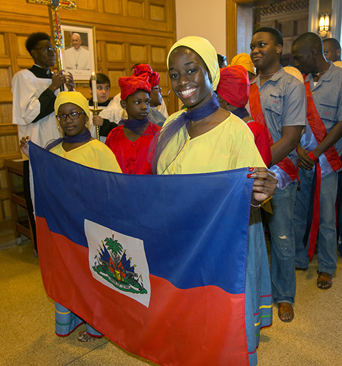 Laurie Bruno, holding flag in foreground, and other members of the Haitian Apostolate, prepare to walk in the procession at the start of the Mass.