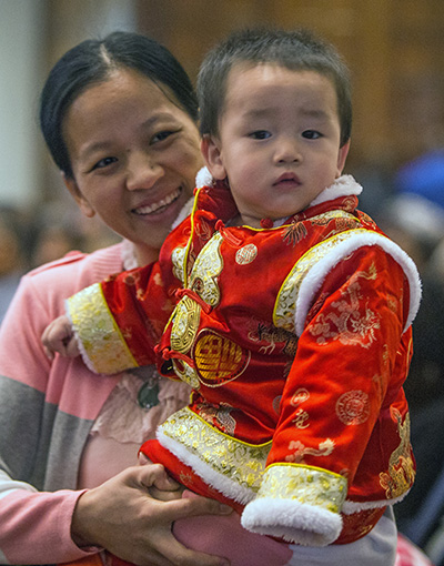 Jindie Lin of the Chinese Apostolate holds her son, Kenny jiang, 13 months old, during Mass.