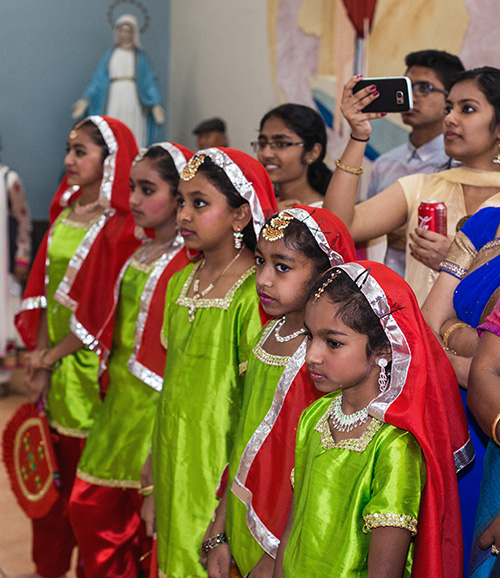Young members of the Indian Apostolate prepare to perform an traditional dance at the reception that followed the Migration Mass.