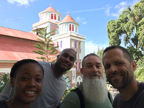 From left: Pascale Reseau, Courtney Bloom, Marcel Navarro and Andres Novela pose for a selfie with the Cathedral of Port de Paix, Haiti.