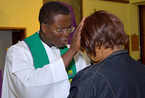 Father Lucien Pierre, pastor of St. Helen Church in Lauderdale Lakes, blesses a worshiper during the black Catholic revival there.
