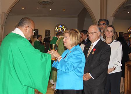 El diácono Victor Pimentel, director espiritual del movimiento Matrimonios en Victoria le da el vino a Beatriz Harriman, durante la Misa por el 20 aniversario del movimiento. Detrás de ella su esposo John Harriman.