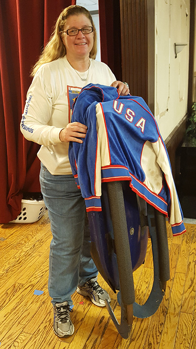 Toni Damigella poses with her luge sled and Olympic jacket.