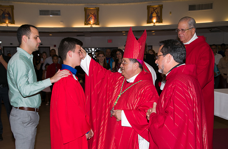 Auxiliary Bishop Enrique Delgado imparts the sacrament of Confirmation on students from Mother of Christ School in Miami during his first confirmation ceremony since being ordained a bishop.