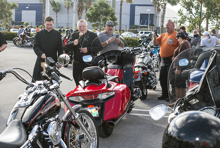 Archbishop Thomas Wenski blesses motorcyclists and their bikes before leading dozens of them on a ride from Our Lady of Guadalupe Church, Doral, to Peterson's Harley-Davidson in Northwest Dade. The annual ride raises funds for Catholic Charities' St. Luke's Center, a rehabilitation facility for those addicted to drugs and alcohol.