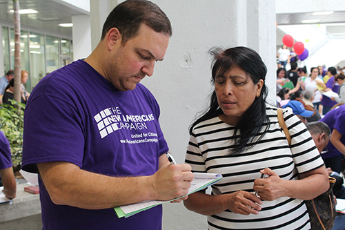Albert Miranda, a volunteer at the New Americans Campaign Mega Citizenship Workshop and Miami Dade College student, assists Concepcion Mendoza De Obando from Nicaragua with her the citizenship application.