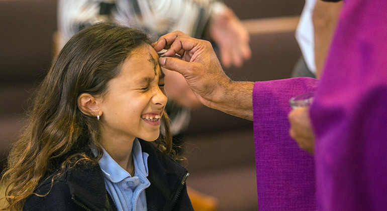FILE PHOTO: Brianna Puglisi, 9, a second-grader at St. Rose of Lima School in Miami Shores, grimaces as St. Rose's pastor, Father George Packuvettithara, marks her forehead with ashes during Ash Wednesday Mass Feb. 14, 2018.