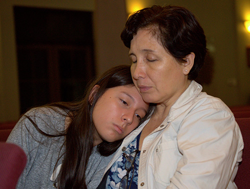A mother and daughter pray at Mary Help of Christians Church, Parkland, during a service Feb. 15 for victims of the Feb. 14 shooting at a nearby high school.