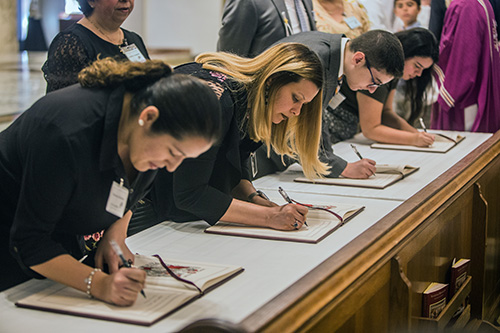 Catechumens sign the Book of the Elect during the Rite of Election ceremony Feb. 18. Archbishop Thomas Wenski accepted 447 catechumens as