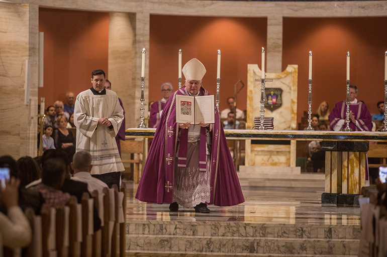 Archbishop Thomas Wenski walks through the cathedral holding up one of the books on which the