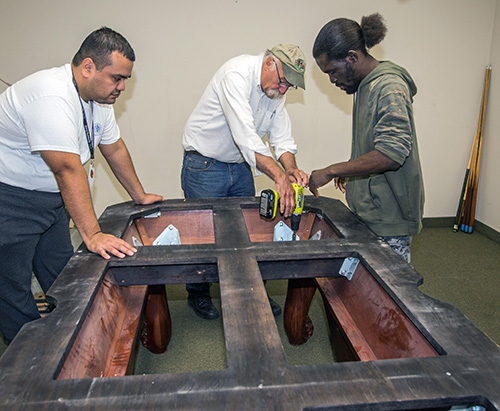 Billiards by Brandt owner Dan Brandt, center, works with Marian Center adult day training students Anthony Castellon, left, and Eric Cowherd as they assemble a billiard table at the center.