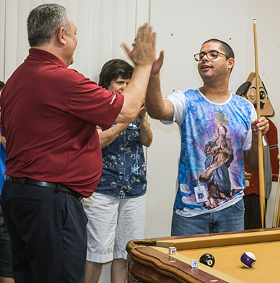John DiToro, professional billiard player, high fives Marian Center adult training center student Rafael Oliveira after a good shot.