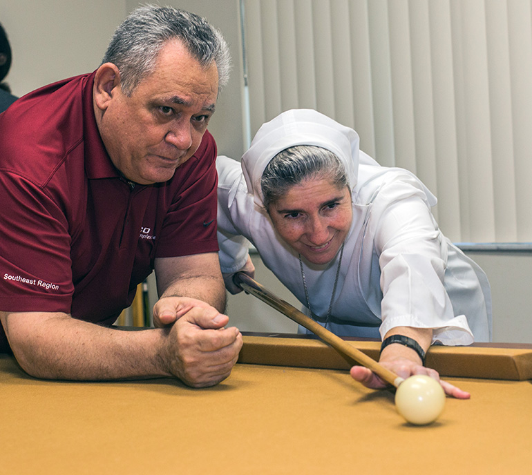 Professional billiard player John DiToro watches as Sister Filomena Mastrangelo, of the Sisters of St. Joseph Benedict Cottolengo, prepares to hit the ball with a cue.