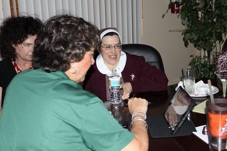 La Hna. Karla Icaza (derecha), asistente ejecutiva de la Oficina del Arzobispo, que no es usuaria de Facebook, mira en un dispositivo electrónico una página de esta red social con Kathleen Bost, administradora de la Oficina de Propiedades y Construcciones, y Mary Ross Agosta (detrás), directora de la Oficina de Comunicaciones, durante la charla informativa sobre