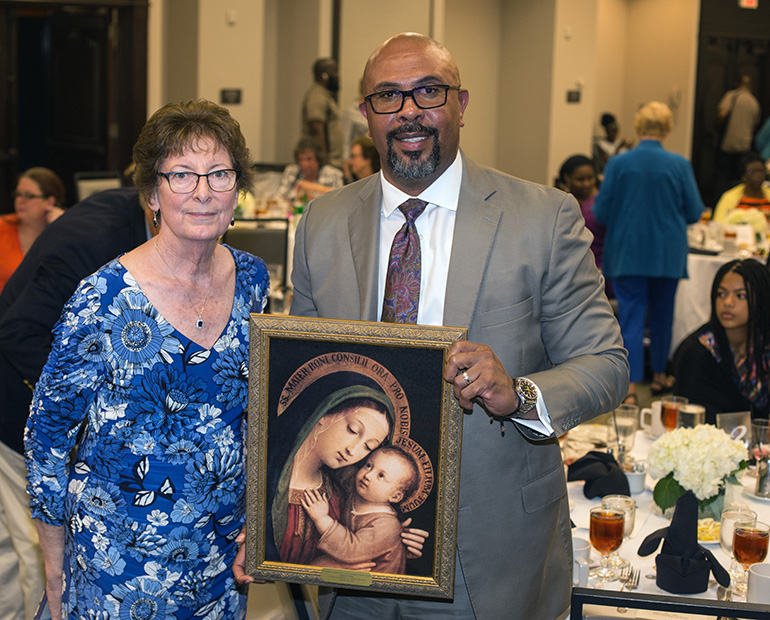 Mary Weber, chair of the MACCW Scholarship Committee, poses with Richard Jean, Archbishop Edward A. McCarthy High School principal, after presenting him him with an image of the Virgin Mary with Jesus.  Jean was this year's honoree as someone who has