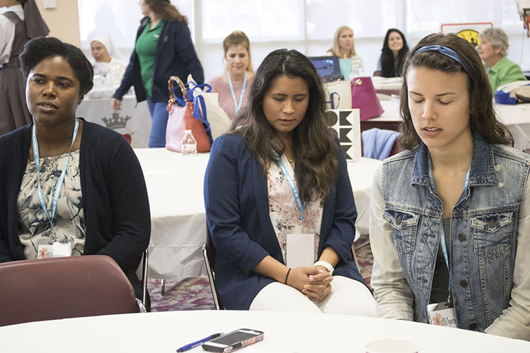 Participants Rachael Sosu, Johana Jesteadt, and Francesca Rieth participate in a moment of meditation during the Women's Health and Fertility Seminar at St. Thomas University Feb. 24.