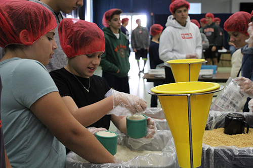Fifth graders and cousins Sofia Lambert, a student at St. Patrick School, Miami Beach, and Kate Caballero, a student at Gulliver Prep, prepare their cups of rice for pouring into the meal bags.
