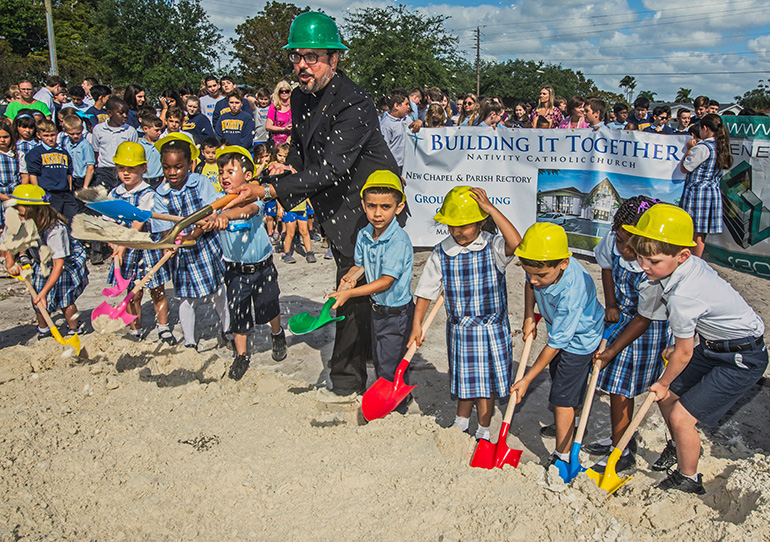 Father David Zirilli, Nativity pastor, and kindergarten students turn the earth with their shovels at the groundbreaking March 28 for a new building housing a new rectory and a chapel at the parish.