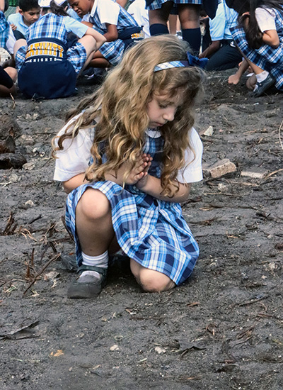 Kindergartener Megan Tane, 6, prays a Hail Mary after she and other Nativity students buried Miraculous Medals in the ground where a new rectory and chapel will be built for Nativity Parish in Hollywood.