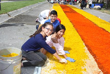 Los niños Marvea Chacon, Coni Sanchez y Edward, ayudan en la elaboración de la alfombra para la procesión de Viernes Santo en la parroquia Corpus Chisti, en Miami.