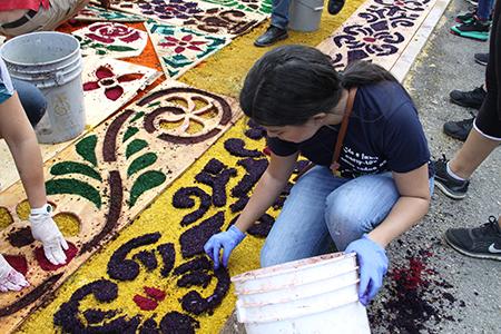 Viviana Gutiérrez, de origen venezolano, ayuda en la elaboración de la alfombra. Desde que llegó hace un año de su país está involucrada en las actividades de la iglesia y pertenece al grupo juvenil como lo hacía en Barquisimeto.