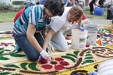 Dos voluntarias que ayudan a elaborar la alfombra para la procesión de Viernes Santo en la parroquia Corpus Christi rellenan con aserrín de colores las imágenes que fueron diseñas y cortadas en madera.