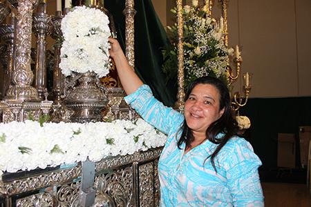 María Pérez, feligresa de la parroquia Corpus Christi, decora con flores el anda de la Virgen de la Macarena que saldrá en procesión la noche del Viernes Santo.