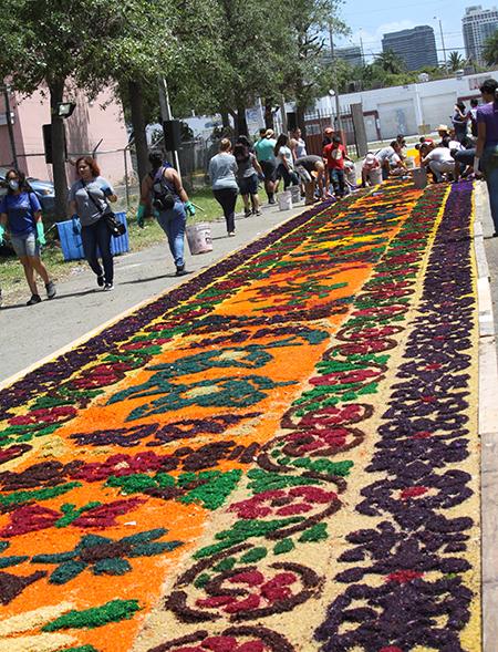 La elaboración de la alfombra para la procesión de Viernes Santo en Corpus Christi empieza muy temprano ese día con el apoyo de cientos de voluntarios, devotos de la Virgen de la Macarena y el Cristo Cautivo de Medinaceli.